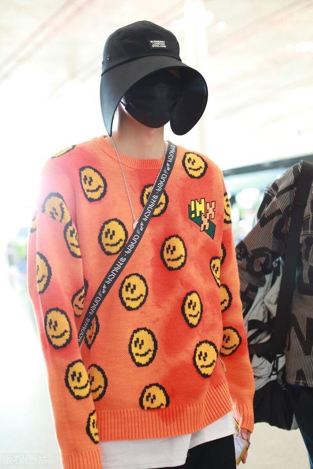 木子洋穿笑脸橘色针织衫现身,戴遮阳帽口罩包