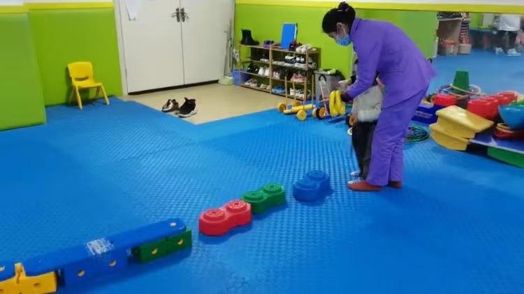 感统老师正在协助孩子训练